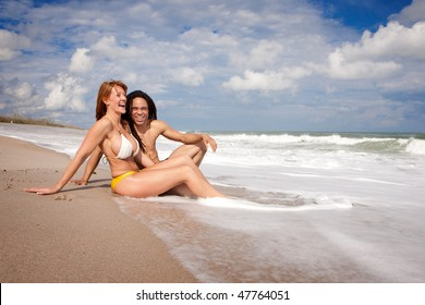 Couple sitting on the beach in waves