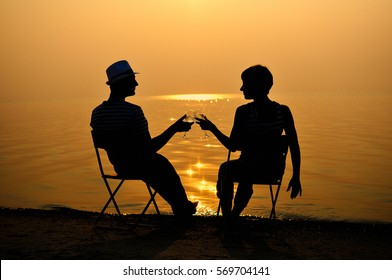 couple sitting on the beach, wine at sunset, silhouettes