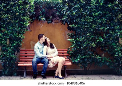 Couple sitting on a bench among green plants enjoying summer and love. Tender hug and looking at the same direction