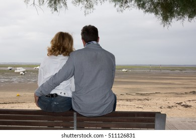 Couple sitting on the bench on the coast with the sea in the background