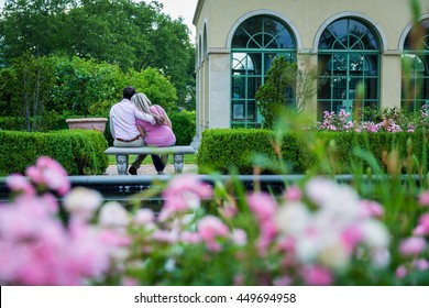 Couple sitting on a bench in a garden