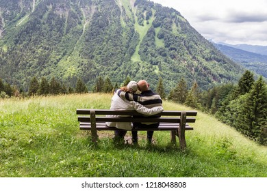 Couple sitting on a bench looking at the alpine landscape in the  Allgau. Bavaria. Germany.
