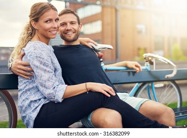Couple sitting on a bench looking into the camera