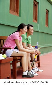 Couple sitting on bench, looking away, smiling