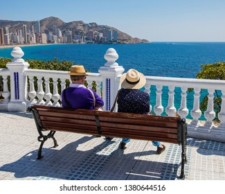 A couple sitting on a bench at Placa del Castell overlooking Levante Beach in Benidorm, Spain.