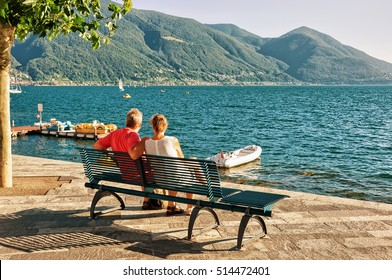 Couple sitting on the bench at the promenade of the luxurious resort in Ascona on Lake Maggiore, Ticino canton, Switzerland.