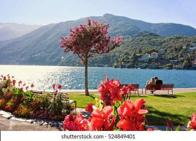 Couple sitting on the bench at the promenade of the expensive resort in Ascona on Lake Maggiore, Ticino canton, Switzerland.