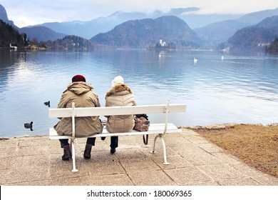 A couple sitting on a bench on the shore of lake