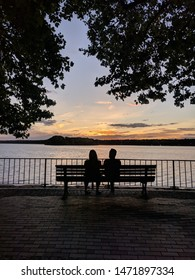 Couple sitting on a bench, silhouette sunset photo. Trees and pier. Mountains, clouds in the background