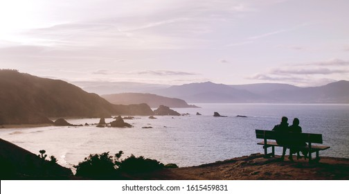 Couple sitting on a bench watching the sea in Loiba Cliffs, Orti