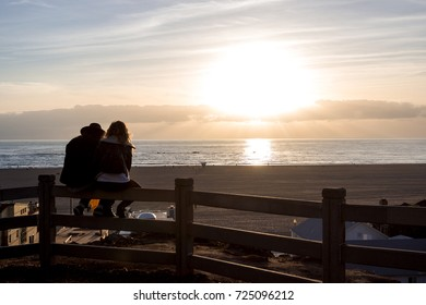 A couple sitting on the bench watching the sunset on Santa Monica seaside. Santa Monica, Los Angeles, United States
