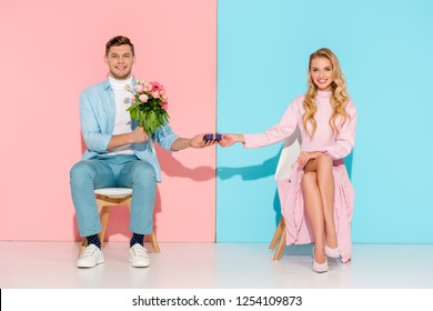 couple sitting on chairs while man presenting gift box with flower bouquet to smiling woman on pink and blue background