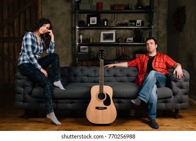 couple is sitting on the couch with a guitar. Long hair of a brunette with an acoustic guitar. Home sofa interior. Checkered shirts and jeans. Evening in living room.