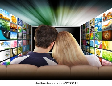 A couple is sitting on a couch watching a flat screen television with photo images. The tv has a glowing light coming out the top. Use it for a media, entertainment, technology or date night concept.