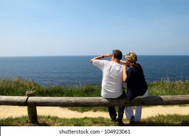 Couple sitting on fence enjoying panoramic sea view