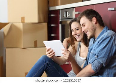 Couple sitting on the floor of the kitchen and buying online with a tablet and moving home