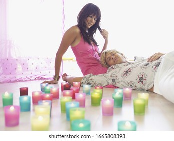 Couple sitting on floor next to lit candles