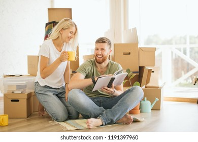 Couple sitting on floor reading book with boxes in the living room. Moving house couple relax lifestyle at home concept