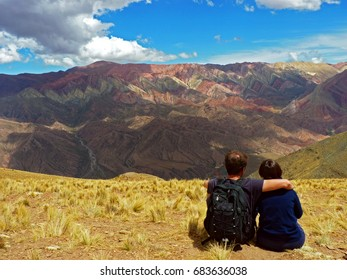 A couple sitting on the grass and looking at the mountains on the other side of the valley. A man with a black backpack hugging a woman. The picture was taken in Huamahuaca, Argentina