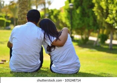 A couple sitting on grass thinking
