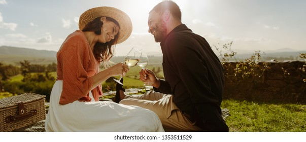 Couple sitting on grass in a vineyard toasting wine. Smiling woman in hat sitting with her boyfriend drinking wine and talking to him.