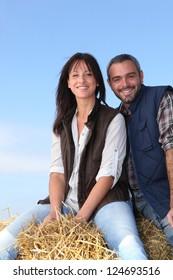 Couple sitting on haystack