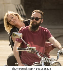 Couple sitting on his retro motorcycle at old town bridge
