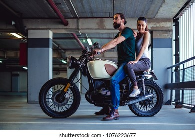 Couple sitting on a motorcycle in a garage. She is smilind and leaning in him
