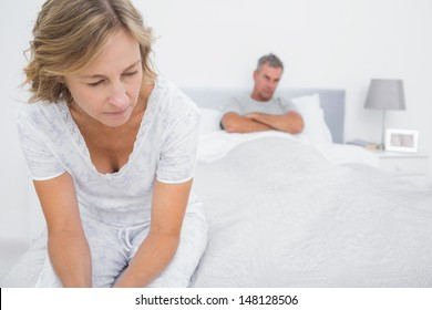Couple sitting on opposite ends of bed after a fight at home in bedroom
