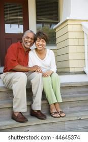 Paar sitzend auf den Außenteilen des Hauses lächeln. Vertikal gerahmte Aufnahme.