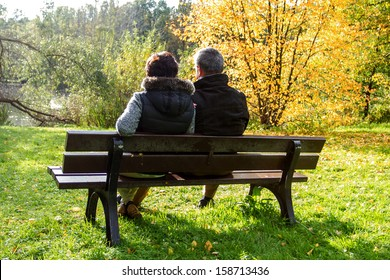 Couple sitting on a park bench in the autumn sun