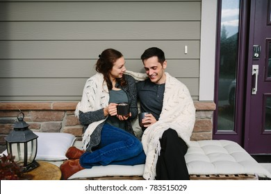 Couple sitting on porch cuddling and drinking coffee