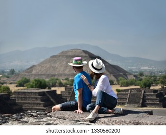 Couple sitting on Pyramid of the Moon and overlooking Pyramid of the Sun in Teotihuacan, Mexico. Anonymous back view of young people travelling for there summer vacations.