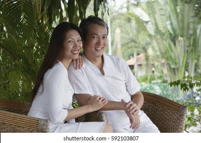 Couple sitting on rattan chairs, looking at camera, smiling