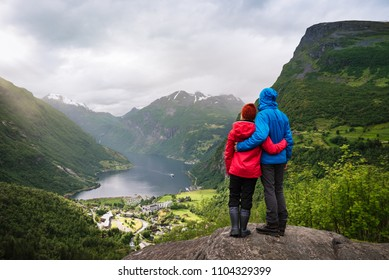 Couple sitting on a rock with looking at the fjord and mountains. Tourist village of Geiranger and the Geirangerfjord, Norway