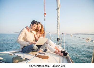 Couple sitting on a sailing boat looking at laptop computer - Beautiful woman and attractive man having fun on a boat while on vacation