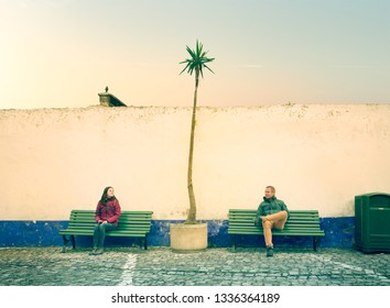 Couple sitting on separate banches. Portugal