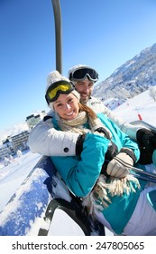 Couple sitting on ski resort chairlift
