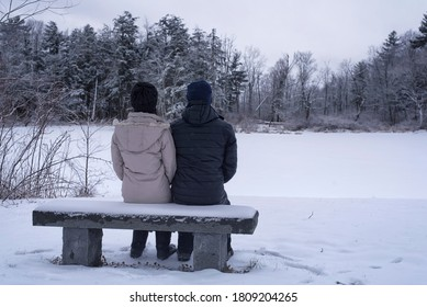 A couple sitting on a snow covered bench overlooking a frozen pond within the white memorial conservation area in Litchfield Connecticut on a cold snowing winter day in new england.