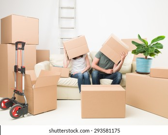 couple sitting on sofa with boxes on their heads, in new house
