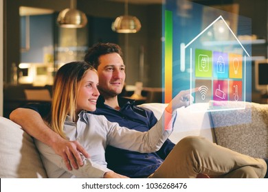 A couple sitting on the sofa controls all the functions of the house such as wi-fi, heating, lighting, television through holography. Concept of, home automation, automations, future, technology.
