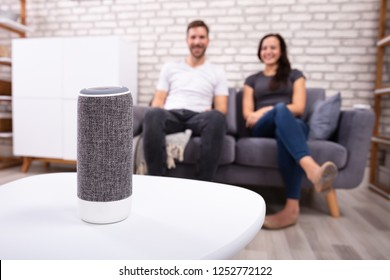 Couple Sitting On Sofa Listening To Music On Wireless Speaker