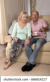 Couple sitting on a sofa using a remote TV controller