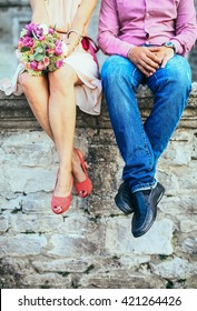 A couple sitting on a stone wall in jeans wearing shoes. Shot from the legs down.