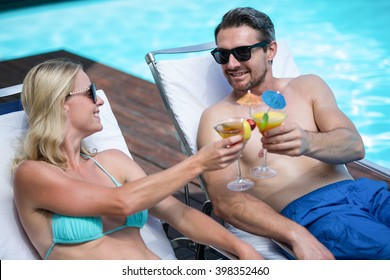 Couple sitting on sun lounger toasting cocktail near the pool