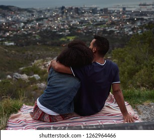 Couple sitting on top of hill looking down at the city lights coming on, romantic date viewpoint