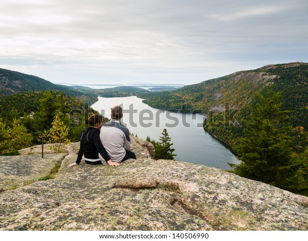 Couple sitting on top of a mountain over Jordan Pond lake in Acadia National Park