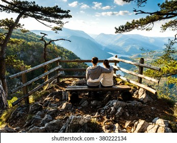 Couple sitting on a viewing platform in Serbia. Stunning views from a cliff into the river Drina Serbia through the pines.