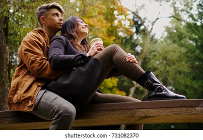 Couple sitting on wooden bridge in autumn park