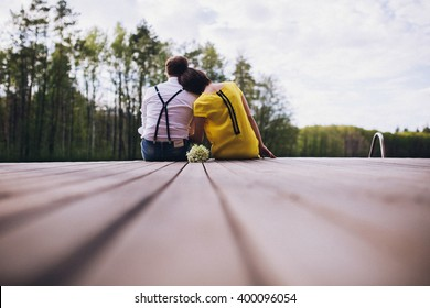Couple sitting on the wooden pier, and looks into the distance. Romance, back view